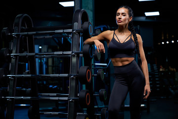 Woman leaning on stand with barbells.