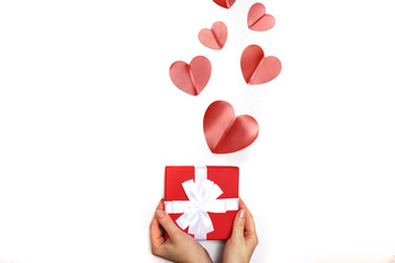 hands of a young woman holding a present box with red hearts on a white background