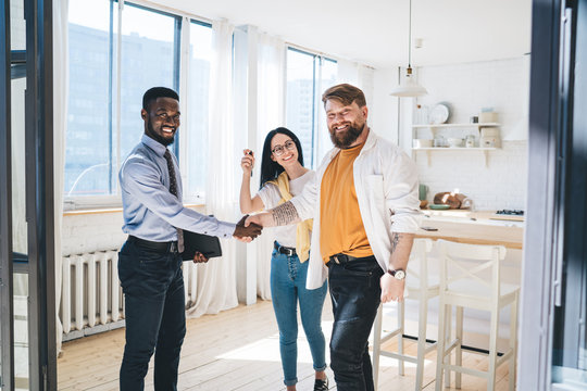 Black realtor and happy couple sealing deal by shaking hands