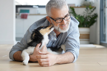Man with puppy dog at home