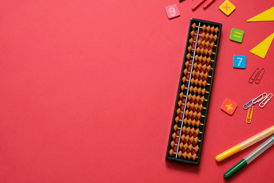 Mental arithmetic and math concept: colorful pens and pencils, numbers, abacus scores on red background, copy space