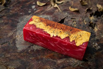 Casting red epoxy resin burl wood cube on old table art background