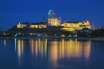 View of Esztergom Basilica from opposite bank of Danube in dusk, Hungary. The Primatial Basilica of Blessed Virgin Mary Assumed Into Heaven and St Adalbert is the biggest building in the country.
