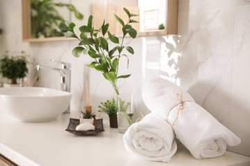 Towels and green plants on white countertop in bathroom. Interior design