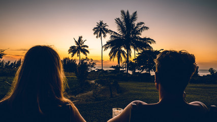 a couple man and a woman watching the sunset with palmtrees in Tanzania Africa Fototapete