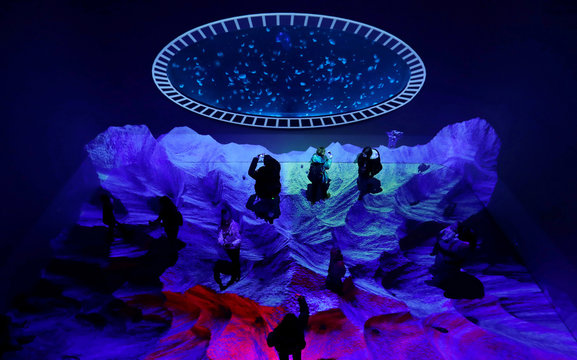 Visitors look at jellyfish swimming in a giant spherical tank