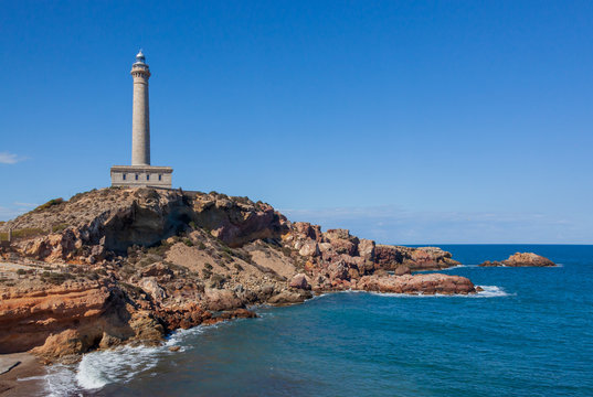 Cabo de Palos Lighthouse on the blue sky background, located on a small peninsula in Cartagena, Murcia, Spain