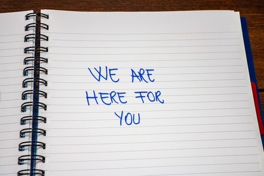 We are here for you handwriting  text on paper, on office agenda. Copy space.