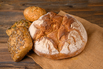 One fresh whole grain bread and various healthy buns from the baker on a jute fabric on a rustic wooden background.