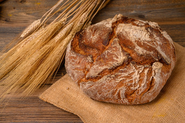 One fresh whole grain bread from the baker on a jute fabric with grain ears on a rustic wooden background.