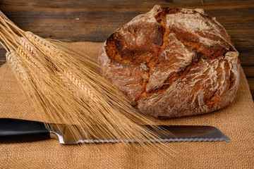 One fresh whole grain bread from the baker and bread knife on a jute fabric with grain ears on a rustic wooden background.