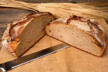 One fresh whole grain bread from the baker, halved with a bread knife on a jute fabric with grain ears on a rustic wooden background.
