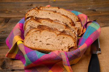 Freshly sliced bread in a bread basket on a jute fabric placed on a rustic wooden background.