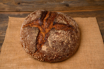 A fresh whole grain bread from the baker on a jute fabric on a rustic wooden background