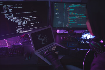 Unrecognizable young man surrounded by multiple screens programming or hacking security in dark room, copy space