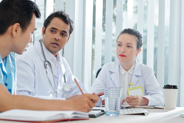 Concerned physicians looking at coworker talking about spread of epidemic