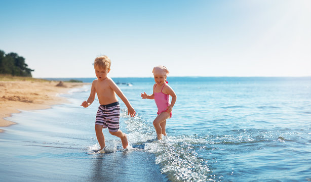 Boy and girl playing on the beach on summer holidays