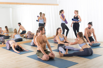 Fotorolgordijn Ontspanning Group of young sporty attractive people in yoga studio, relaxing and socializing after hot yoga class. Healthy active lifestyle, working out indoors.