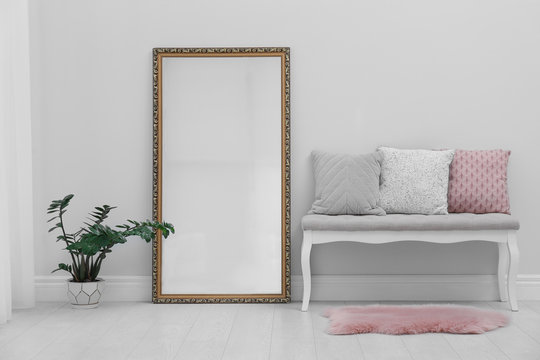 Modern large mirror and comfortable bench near light wall in room