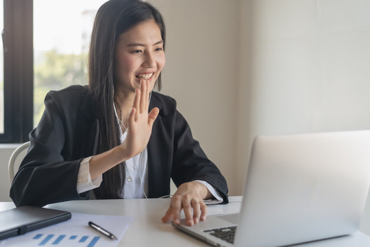 Happy young asian business woman waving hands to greeting partner during making video conference with her team.