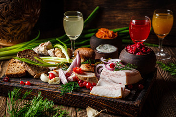 European cuisine in Ukrainian style. Meat set of homemade sausage, lard and bread. Serving dishes in a restaurant on wooden board with alcoholic drinks. background image copy space