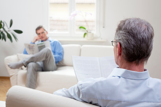 Two mature men sitting in a living room and reading newspaper
