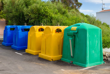 A row of colorful dustbins for waste segregation.