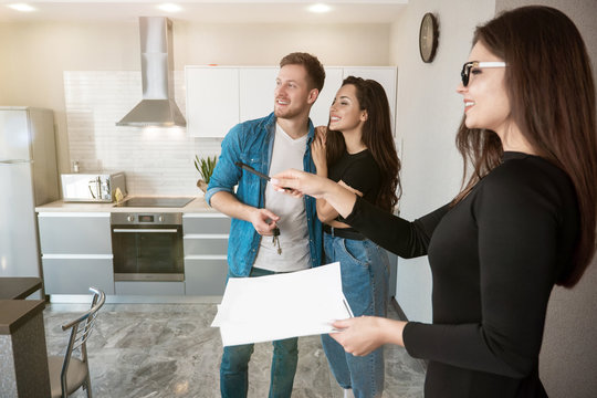 attractive woman realtor property manager showing new apartment for rent to young beautiful couple husband and wife