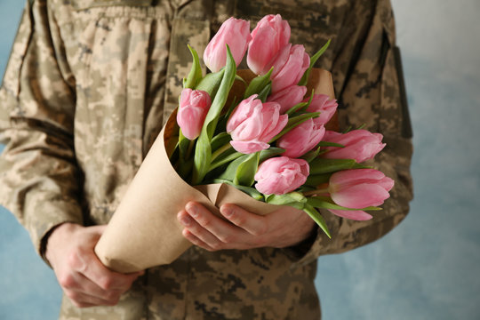 Man in military uniform holding bouquet of tulips on blue background, close up