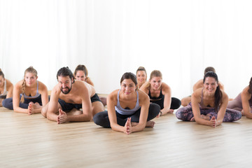 Fotomurales - Group of young sporty attractive people in yoga studio, practicing yoga lesson with instructor, sitting on floor in forward band stretching yoga pose. Healthy active lifestyle, working out in gym.
