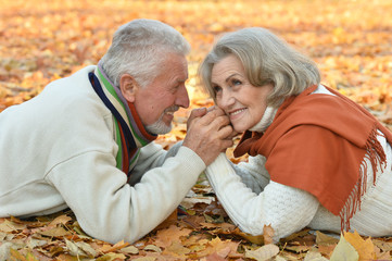 Happy senior couple lying on autumn leaves