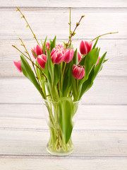 Tulips in vase. White and red spring flowers on wooden background. Bouguet of tulips.