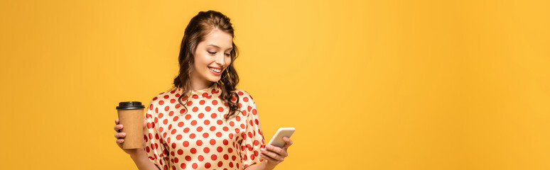 panoramic shot of happy young woman holding coffee to go and using smartphone isolated on yellow