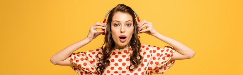 panoramic shot of shocked young woman touching wireless headphones while looking at camera isolated on yellow