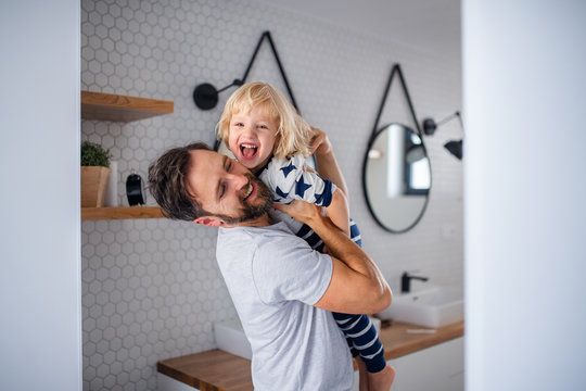 Mature father with small son indoors in bathroom, having fun.