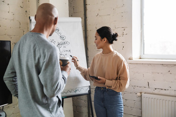 Image of multiethnic young coworkers standing by flipchart in office