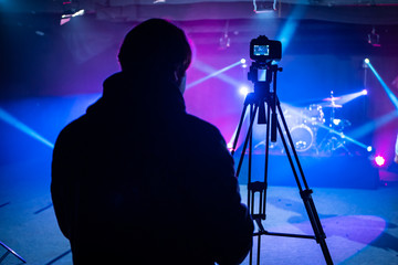 Camera Man or Director operating a Video Camera or DSLR Shooting a music video or concert with stage lighting. Wall mural