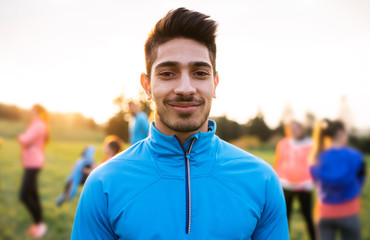A portrait of young man with large group of people doing exercise in nature.