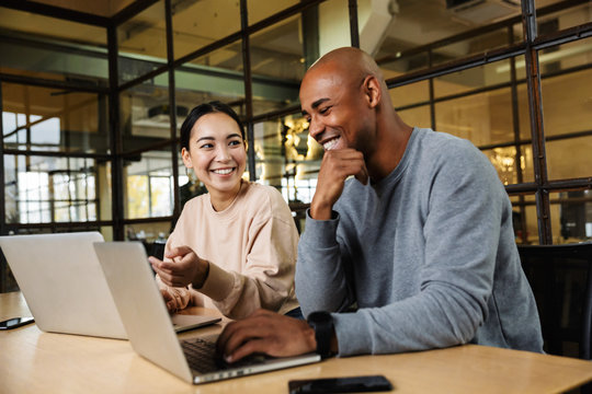 Image of multiethnic young coworkers working on laptops in office