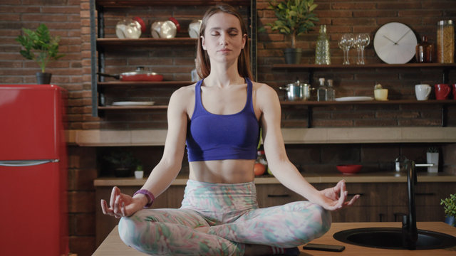 Zooming in close up view of young gorgeous fit woman sitting in lotus pose and deeply mediating, slowly breathing out and opens her eyes, looks straight to camera. Yoga time, meditation, relax