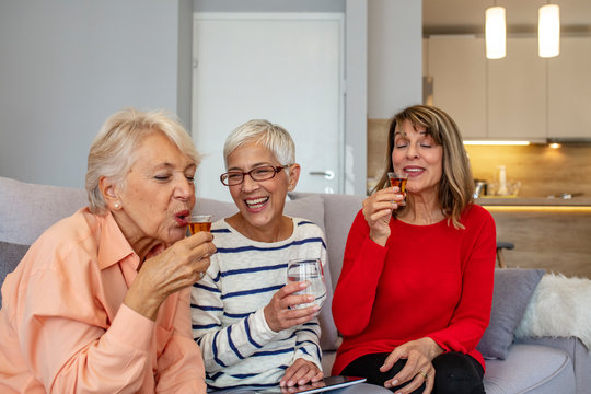 Three beautiful, mature women are sitting at home and drinking brandy. They are having fun, laughing and updating each other on the latest news. Women are between 50 and 65 years old. Cheers!