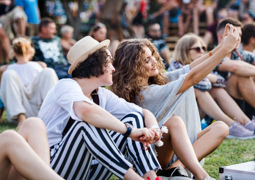 Group of young friends sitting on ground at summer festival.