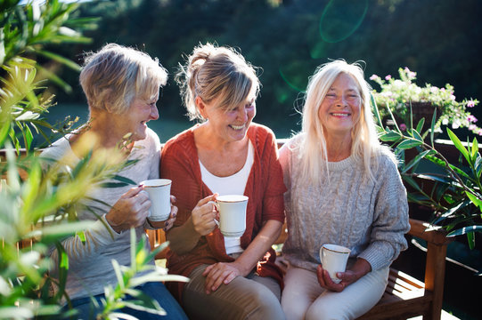 Senior women friends with coffee sitting outdoors on terrace, resting.