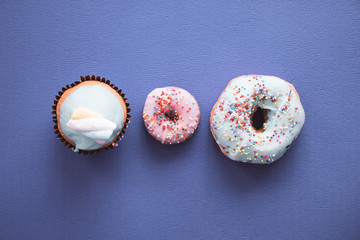 Donuts on a colourful background two donuts and one cupcake with candy on top. top view picture