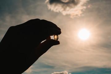 Fototapeta Hand holding fish oil vitamin d transparent capsules. Dietary supplements