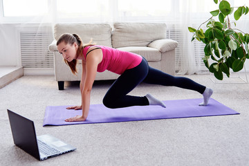 Beautiful young woman doing plank exercise in living room at home, watching videos on laptop computer and repeating online instructions, copy space. Full length side view