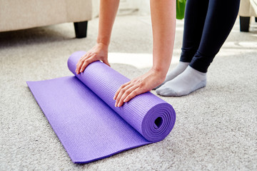 Close up image of woman rolling purple fitness or yoga mat after sport practice, pilates or working...