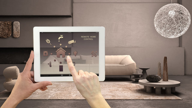 Smart remote home control system on a digital tablet. Device with app icons. Living room with concrete plaster wall, large sofa and fireplace background, architecture interior design