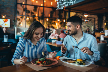 romantic couple in restaurant having lunch