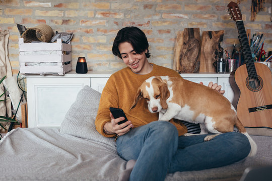 young man using mobile phone in his room, cuddling with his dog